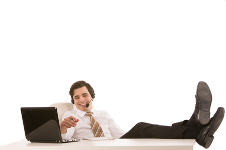 Successful or lazy businessman relaxing at his desk with his feet up on the desktop while talking on a headset photo