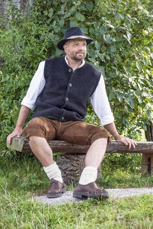 hombre sentado: Hombre sentado en trajes tradicionales b�varos en un banco de madera delante de los arbustos