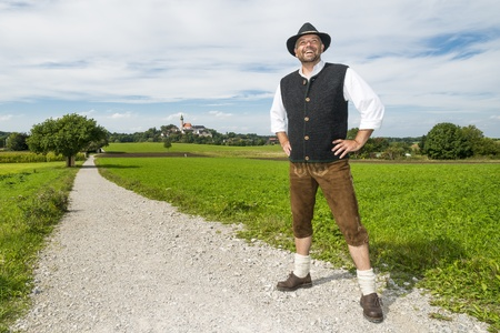 Man standing in Bavarian traditional costume on a sunny day in front of Andechs monastery