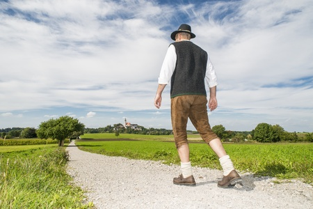 costum: Man in traditional bavarian costum is going to monastery Andechs