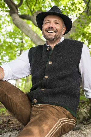 Laughing man in Bavarian costume sitting in a forest on a sunny day photo