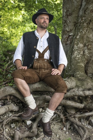 Seated man in traditional Bavarian costumes in forest Stock fotó