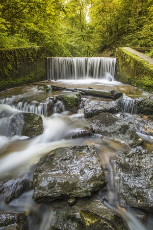 Picture with with white-angle lens of a waterfall in a forest in summer with a long exposure time  Stock Photo