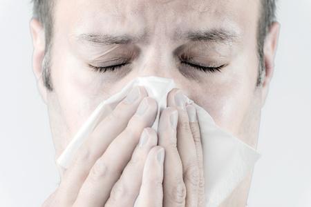 estornudo: Retrato de un hombre enfermo que estornuda en un pa�uelo de papel Foto de archivo