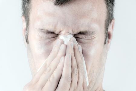 Portret van een zieke man die niezen in een weefsel Stockfoto