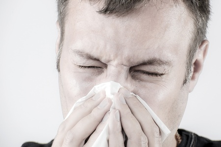 Portrait of a man who is sneezing in a tissue