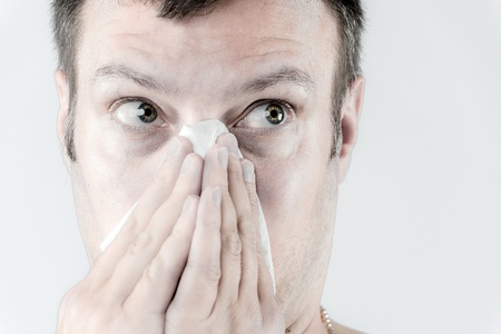 Portrait of a ill man who is sneezing in a tissue