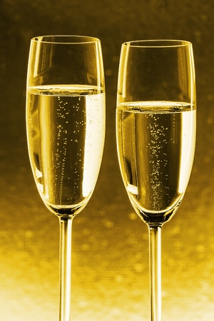 Two glasses of champagne with gold background photo
