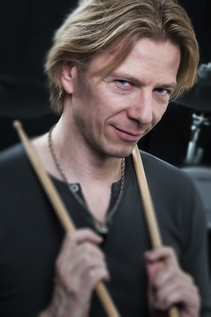 Man in front of a black background an his drums is holding drumsticks and is looking to the viewer photo