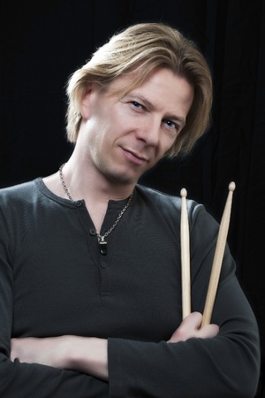 Man in front of a black background an his drums is holding drumsticks photo
