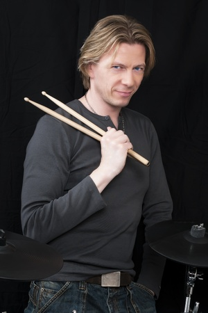 Standing man in front of a black background an his drums is holding drumsticks photo