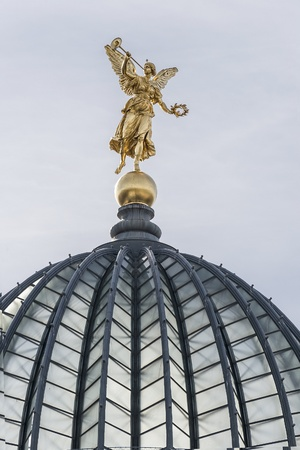 Golden angel with trumpet on the top of historic house in Dresden