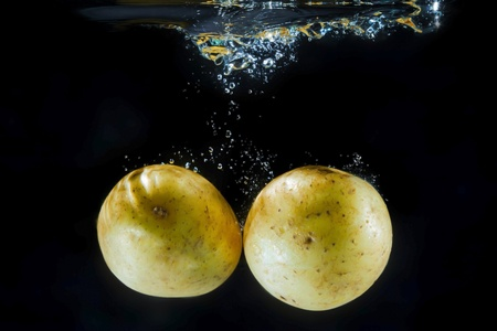 Two yellow potatoes under water with bubbles photo