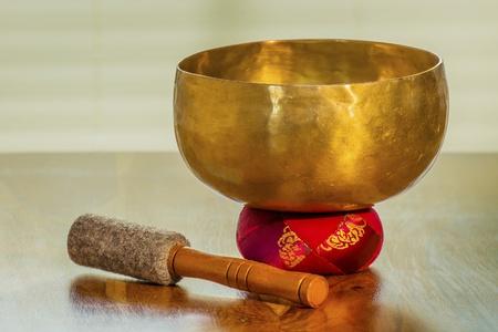 musicoterapia: Ciotola del suono su un tavolo con cuscino rosso