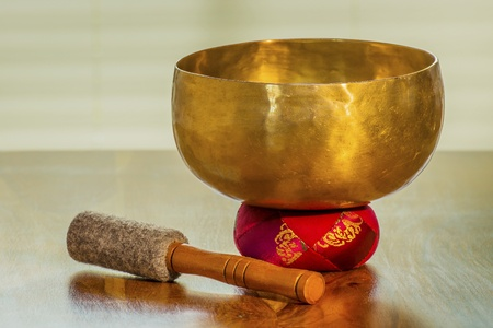 bolster: Sound bowl on a table with red bolster