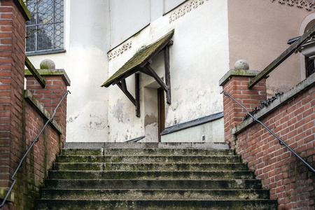 threshold: Stairs to the entrance of a church with red bricks walls in the town Dachau, Germany