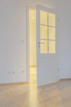 room with parquet floor, open door and light shining