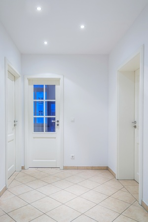 Indoor foyer with white doors, light brown tiled floor, lamps Stock Photo