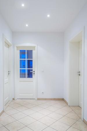 Indoor foyer with white doors, light brown tiled floor, lamps Stock Photo