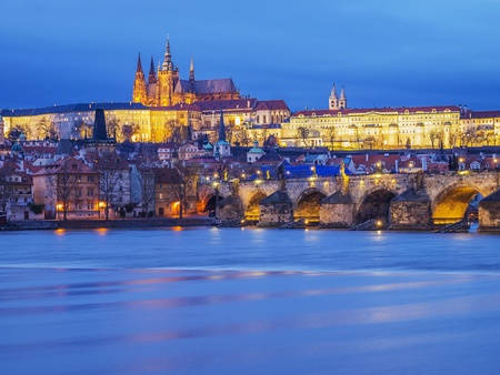 View to illuminated Prague with Charles Bridge, Hradcany Castle and Vitus in the evening at January  photo
