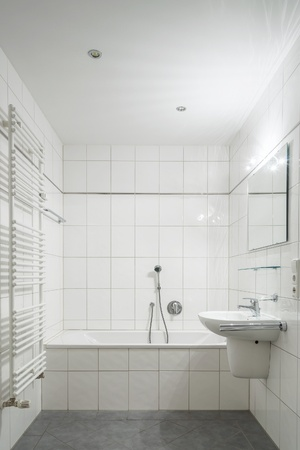 wash basin: White tiled bathroom with toilet, bathtub, sink and mirror