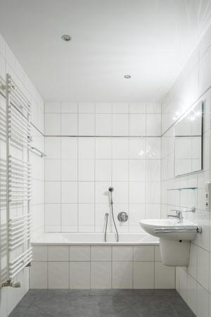 Wit betegelde badkamer met toilet, ligbad, wastafel en spiegel