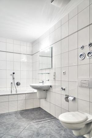 白いタイル張りのバスルーム、トイレ、浴槽、トイレ、ミラー付け