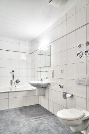 corner tub: White tiled bathroom with lavatory, tub, toilet and mirror Stock Photo