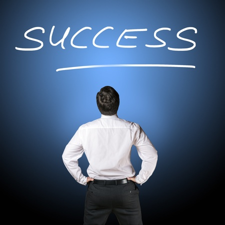 Backside of a business man in black business trousers and white business shirt who is looking to lettering  success  with a blue-black background Stock Photo - 17276330