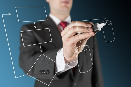 business man on blue background is drawing white empty flow chart regarding computer system process