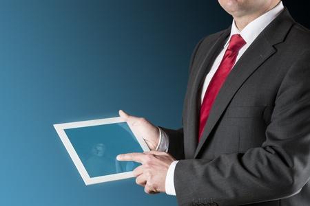 よく服を着てビジネスの男を保持しているタブレット コンピューターの背景はブルー ブラック
