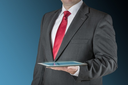Well dressed business man is holding a tablet computer  Background is blue   black Stock fotó - 17286636