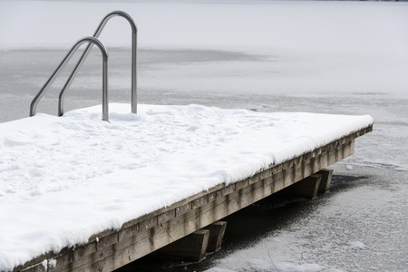 Pool ladder on a frozen lake with snow and ice photo