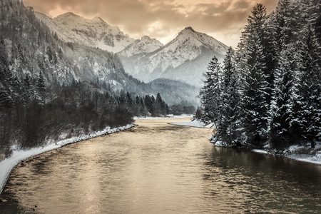 Sunset in a landscape with trees, alps and a river photo