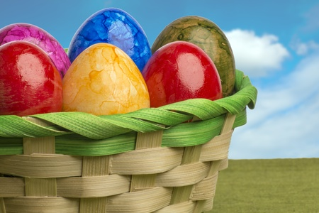 Colored easter egg basket with blue sky and white clouds photo