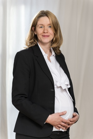 Pregnant blond business woman in black business clothing with light background is looking to the viewer photo
