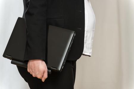 ノート パソコンと明るい背景と黒のビジネス服で妊娠中のブロンドのビジネス女性