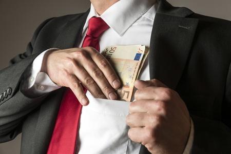 Businessman putting money in his shirt pocket