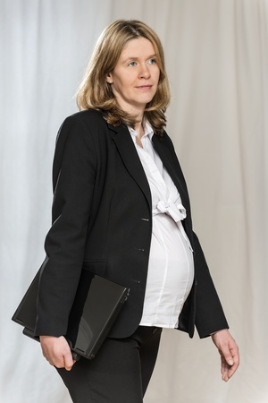 Walking pregnant blond business woman in black business clothing with light background photo