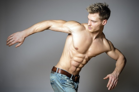 Young and blond athletic man is turning around photo