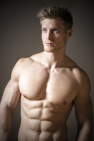 Blond, athletic man with blue eyes and a muscular upper body photo