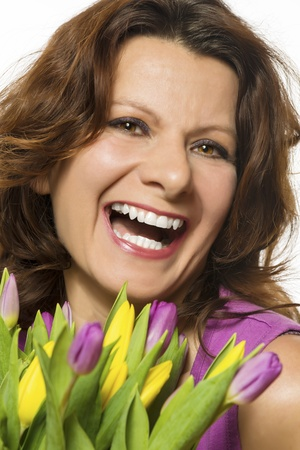 Smiling woman with pink and yellow tulips photo