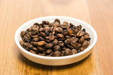 Small white cup of coffee beans on a wooden table photo