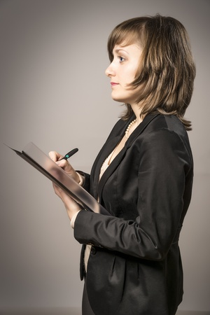 Business woman in black suit takes notes with a pen in a file photo