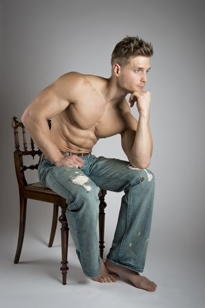 Thinking athlete with well trained muscles sit on a chair photo