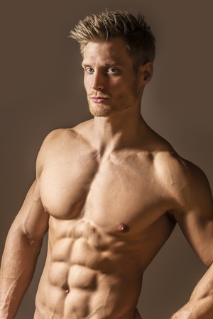 pecs: Portrait of a blonde, blue eyed young man with a very athletic figure and well trained abs and pecs
