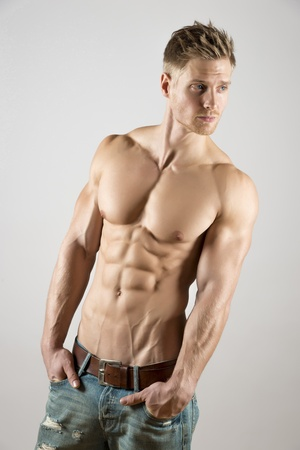Young athete with well trained body, abdominal and pectoral muscle and blue jeans look right