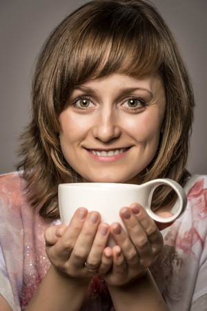 Young woman enjoying tea or coffee in a white cup photo