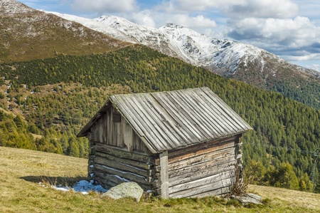 Cottage in the high mountains in South Tyrol on a sunny day with clouds photo