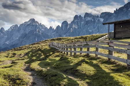 Evening scenery in South Tirol with green meadows, cottage, fence, alps and clouds on blue sky photo